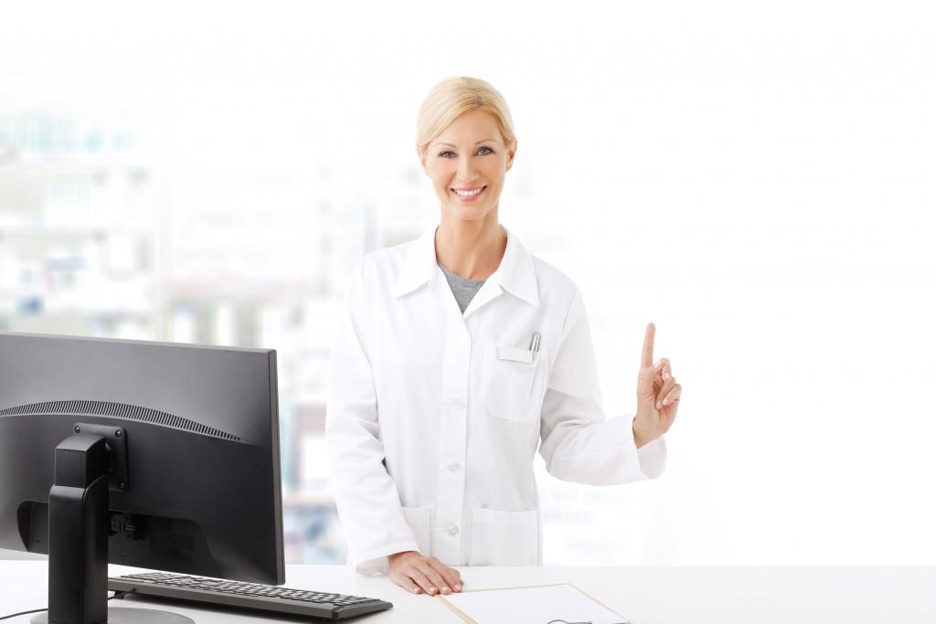 Portrait of middle age pharmacist woman standing at pharmacy. Smiling woman wearing lab coat and working on computer while she shows something with her finger.